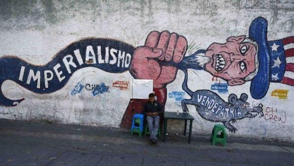 Man sits by a graffiti denouncing U.S. imperialism in Caracas.