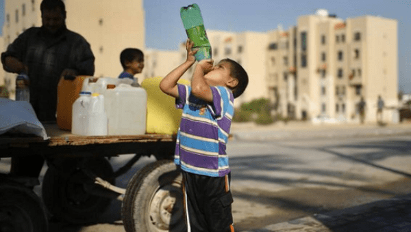 A Palestinian boy drinks water next to a cart loaded with containers filled with water from public taps in the northern Gaza Strip, June 20, 2013.