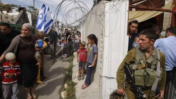 An Israeli soldier stands guard as settlers move into a house disputed by Israeli settlers and Palestinians in the West Bank city of Hebron, April 13, 2014.