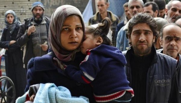 Residents queue up to receive humanitarian aid at the Palestinian refugee camp of Yarmouk, Damascus, Syria, March 11, 2015.