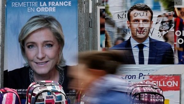 A woman walks past official posters of candidates for the 2017 French presidential election Marine Le Pen and Emmanuel Macron on a local market in Bethune.