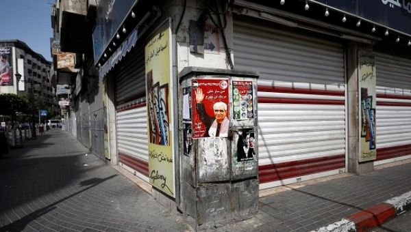 A poster depicting Ahmed Saadat, jailed leader of the Popular Front for the Liberation of Palestine, is seen as shops are closed during a general strike.