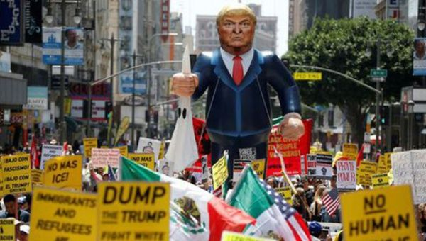 A gigantic Trump effigy is carried down the street during a protest in Los Angeles, CA.