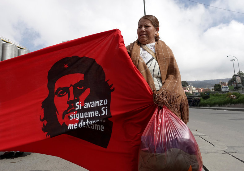 "A retailer of second hand clothes attends a rally during May Day celebrations in La Paz, Bolivia May 1, 2017. The banner reads ""If I advance, follow me, if I stop, kill me""."