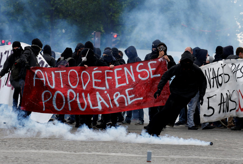 "Tear gas floats in the air as demonstrators walk behind a banner which reads, ""Populist Self-Defence"" during clashes at the traditional May Day labour union march in Paris, France, May 1, 2017."