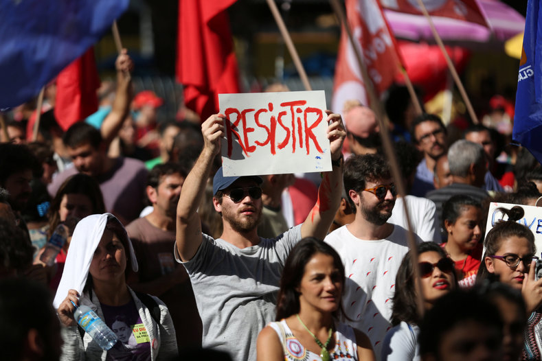 """A man holds a sign reading """"To resist"""" during a demonstration against Brazil"""