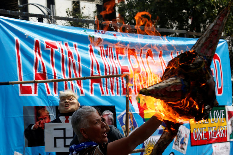 An activist burns a pinata with a picture of U.S. President Donald Trump during a demonstration on International Labor Day in Mexico City, Mexico May 1, 2017.