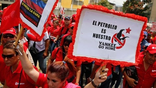 """Workers of state-run oil company PDVSA take part in a 2015 rally against U.S. imperialism. The placard reads: """"The oil is ours, Yankees go home."""""""