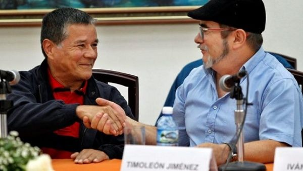 ELN leader Gabina and FARC leader Timochenko shake hands during a joint press conference in Havana, Cuba, May 11, 2017.