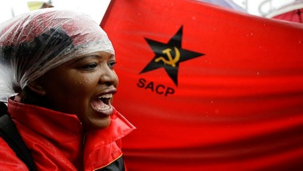 Protester along with a South African Communist Party flag.