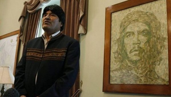 Bolivian President Evo Morales speaks during an interview in front of a portrait of Ernesto