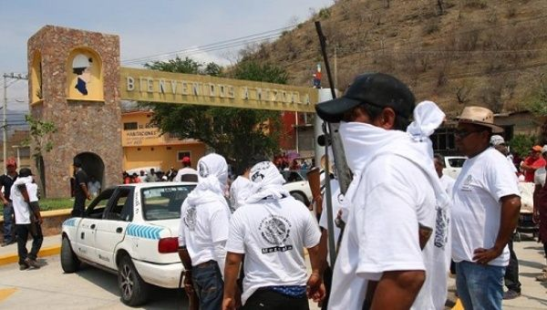 Newly-formed community police block the entrance to Mezcala to protest ongoing violence in the region.