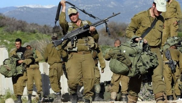 Israeli soldiers carry their belongings in an area near the Israel-Lebanon border Jan. 29, 2015.