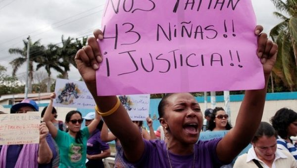 "An activist holds a sign that reads "" We are missing 43 girls. Justice"" during a protest outside of Guatemala"