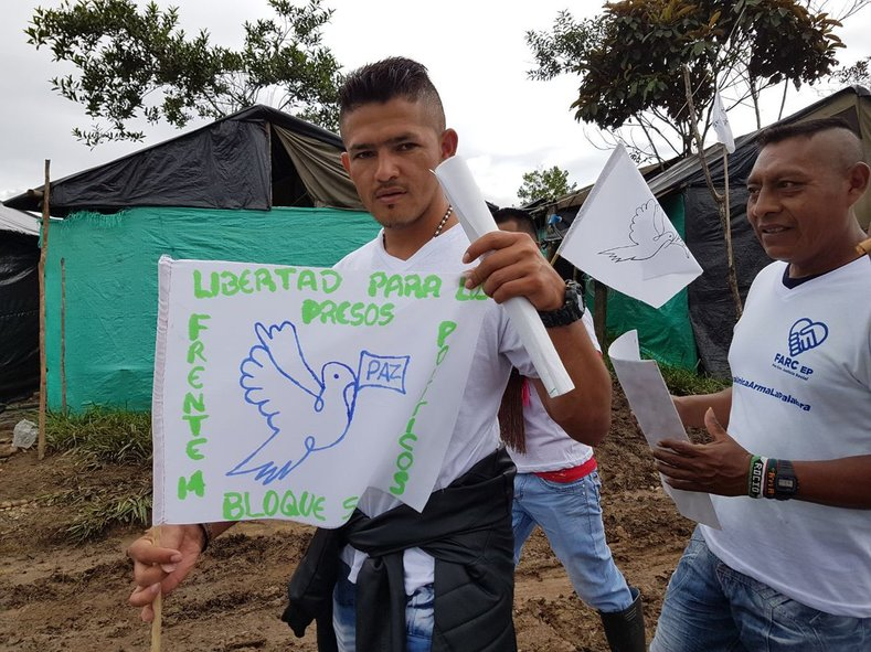 """A FARC supporter holds a sign reading """"freedom for political prisoners,"""" in reference to the thousands of FARC prisoners still awaiting amnesty."""