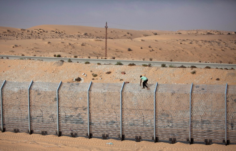 A labourer works on the border fence between Israel and Egypt near the Israeli village of Be