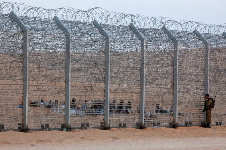 An Israeli soldier stands near the border fence between Israel and Egypt as African would-be immigrants sit on the other side near the Israeli village of Be