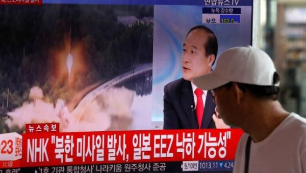 A man watches a TV broadcast on North Korea
