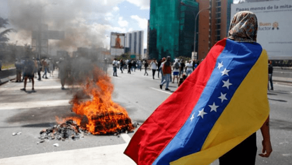 Protesters clash with riot police in Caracas.
