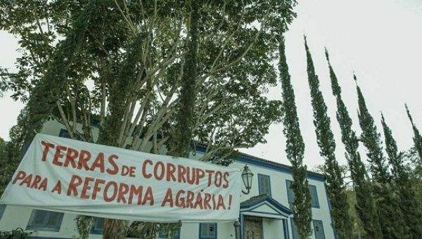 "A sign outside the farm reads, ""Lands of the corrupt for the agrarian reform,"" in Sao Paulo."