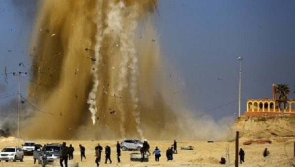 Palestinians run for cover as sand and smoke rise following an Israeli airstrike in the northern Gaza Strip on February 6, 2017