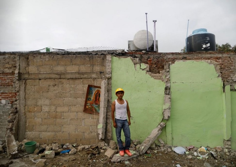 "Jaime Delgado, 21, an agricultural worker whose house was not damaged, said: ""A lady died here, crushed by the rubble. All this is over, now I search pieces of iron to sell. My economic situation is bad."""