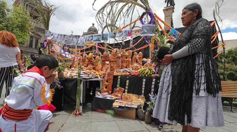 En Bolivia, mujeres indígenas aimaras dispusieron mesas repletas de comidas típicas, flores e imágenes para recordar a los difuntos.