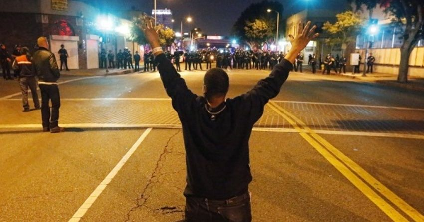 A man kneels in the road in front of a line of police during a demonstration in Los Angeles, California on Nov. 24, 2015 following the grand jury decision in the shooting of Michael Brown.
