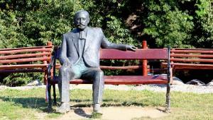 """Kisbacon; Benedek Elek szobra a Barót-patak partján. Itt élt és halt meg Benedek Elek (1859–1929) magyar újságíró, író, országgyűlési képviselő, """"a nagy mesemondó""""."""