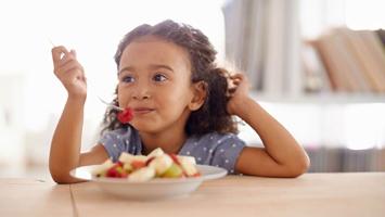 Girl-eating-fruit-salad