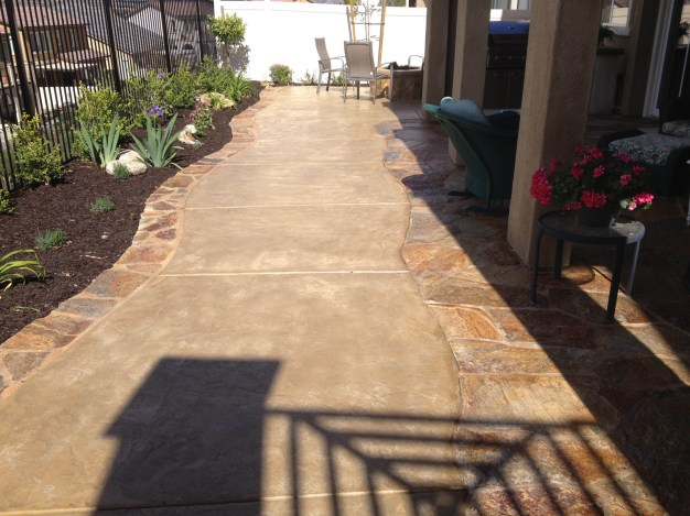 Colored concrete with flagstone border Oval fire pit with sitting wall and colored concrete in Temecula McCabe's Landscape Construction