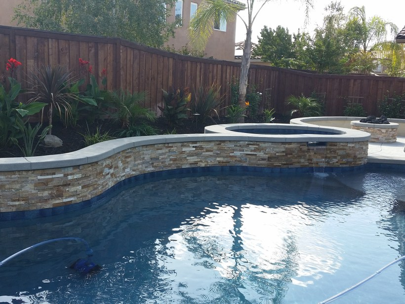 Pool and spa, fireplace, tropical plantings, stone work