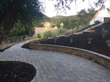 Pavers, wall, planter boxes on hill