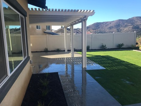 Landscape with grass, patio and cover