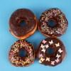 Four sprinkled donuts on blue background