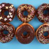 Six sprinkled donuts on blue background