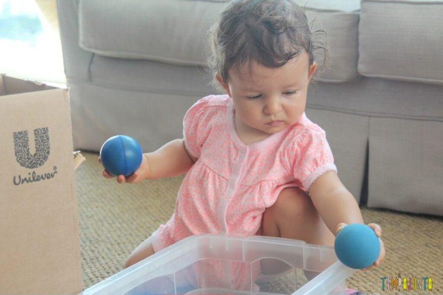 Brincadeira para bebês com bolas e caixas - Gabi com duas bolinhas azuis