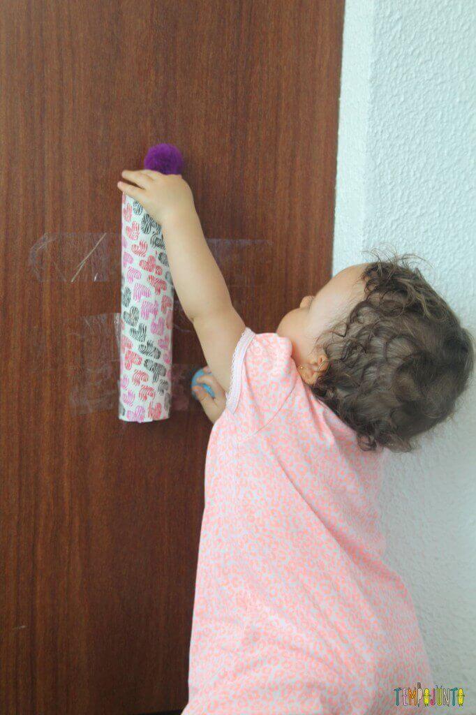 Brincadeira para bebês pompom no tubo-colocando o pompom