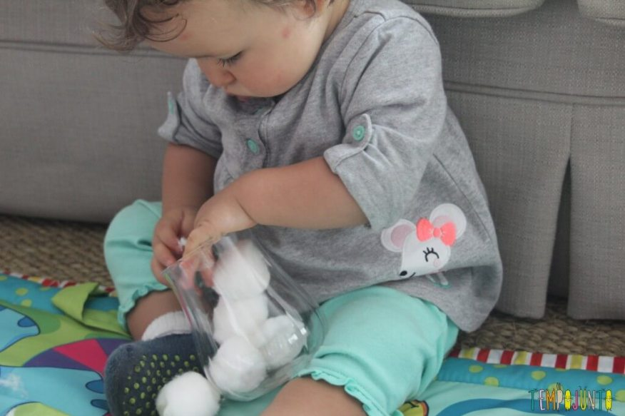 Brincadeira simples para bebês - Gabi concentrada no pote de algodão