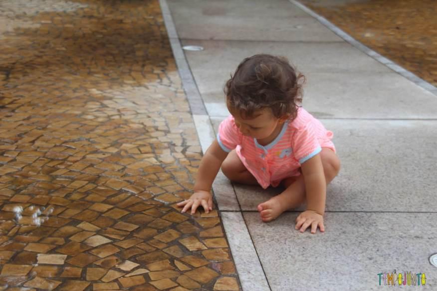 Brincadeira sensorial para bebês nas poças de chuva - Gabi com as mãozinhas na poça