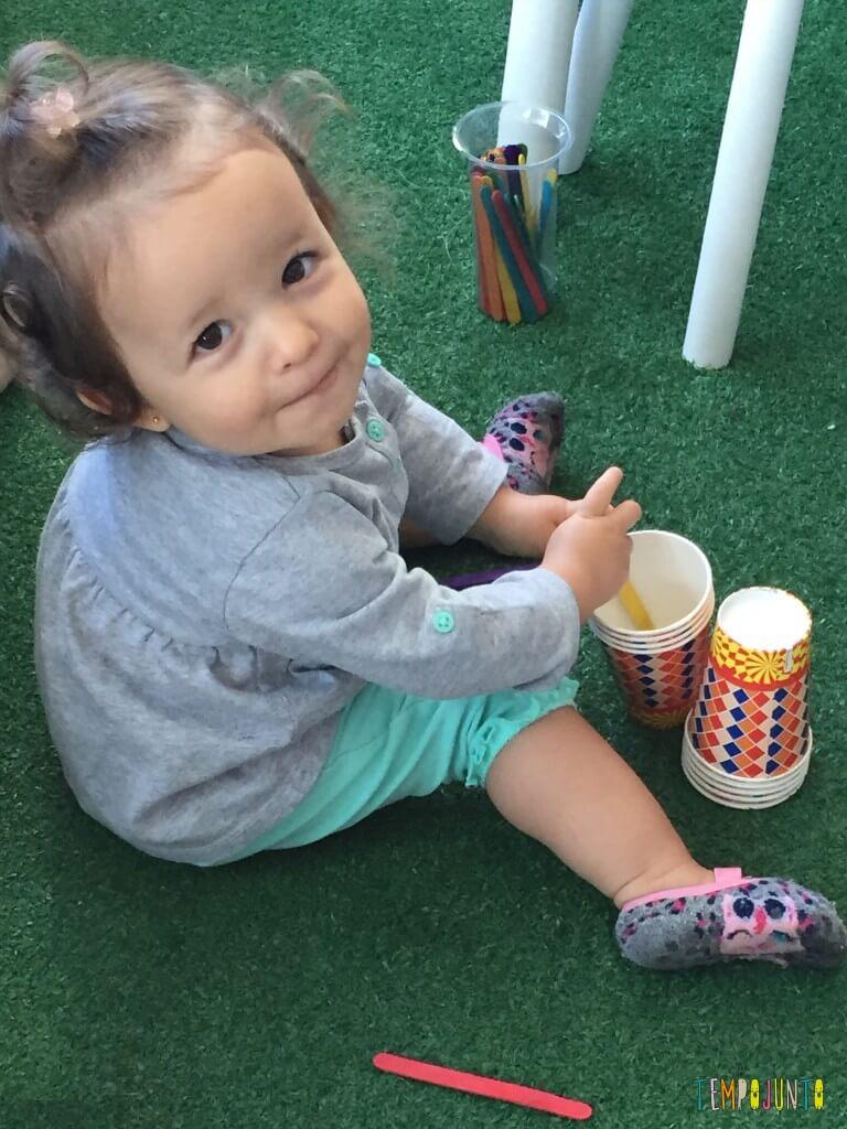 Brincadeira para bebês com copos descartáveis - Gabi guardando palito nos copos