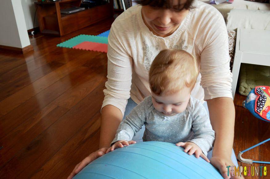 Uma bola de exercício e 5 brincadeiras fantásticas para seu bebê - bebê em pé apoiada na bola 2