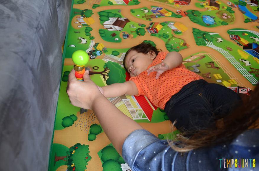 Brincadeira com chocalho para os bebês que começam a rolar - julia de lado