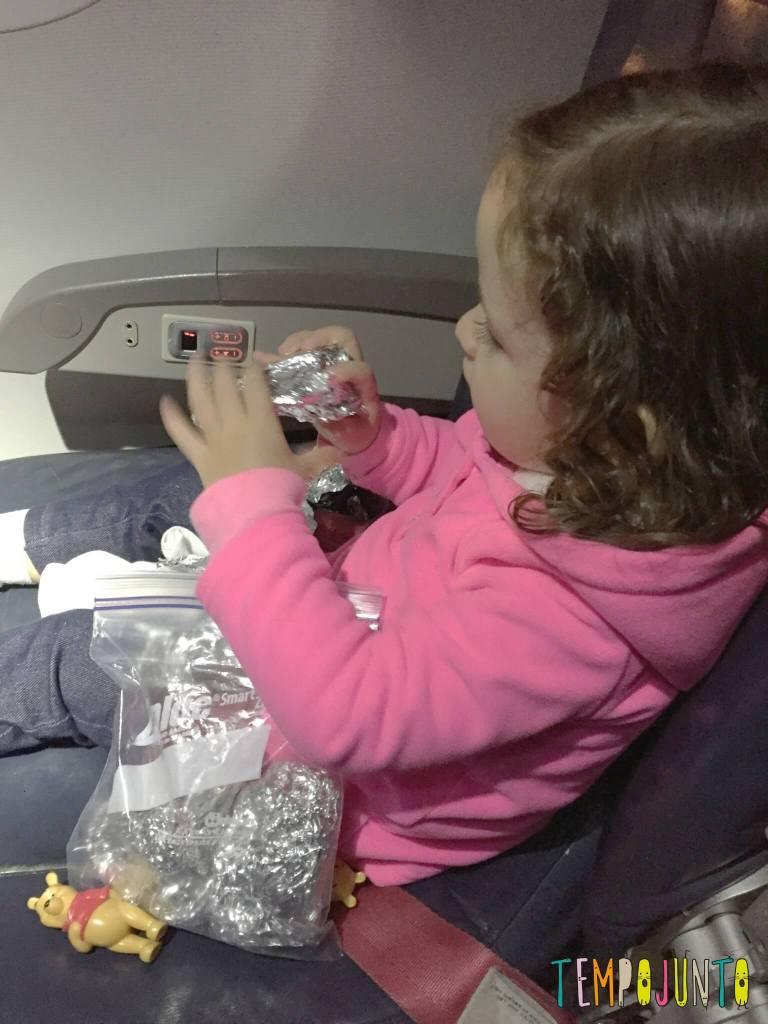 Brincadeiras para fazer no avião com crianças pequenas - gabi desembrulhando o brinquedo de papel aluminio