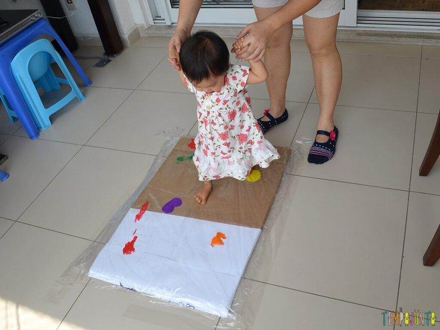 Pintura gigante e sem sujeira para brincar com os bebês_BEBÊ CAMINHANDO SOBRE O PLÁSTICO