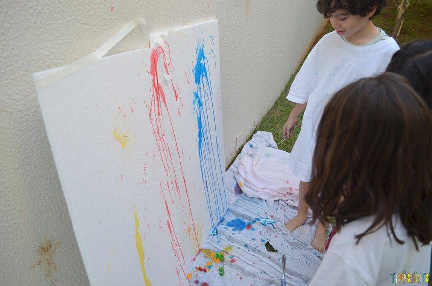 Brincar de pintura com bexiga para um dia ao ar livre - criancas olhando a tinta que explodiu