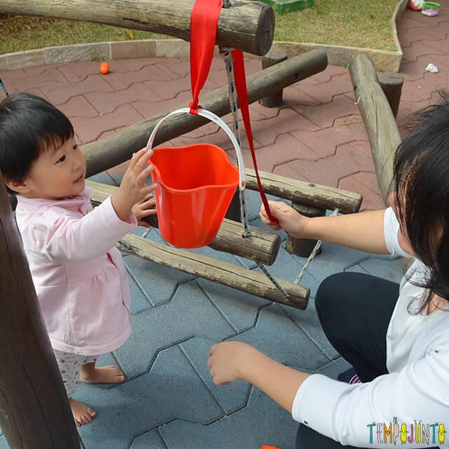 Despertar a curiosidade do bebê com uma brincadeira de causa e efeito - bebe puxando o baldinho