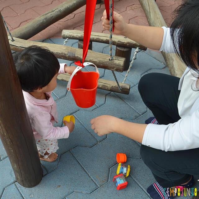 Despertar a curiosidade do bebê com uma brincadeira de causa e efeito - mae e bebe brincando com baldinho