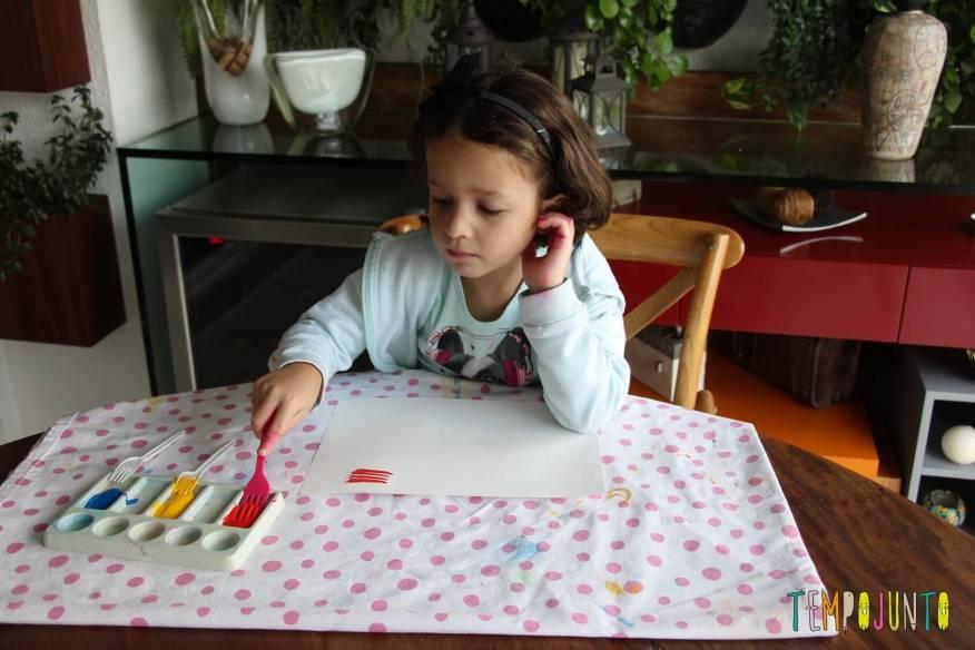 Gabriela pintando com garfo