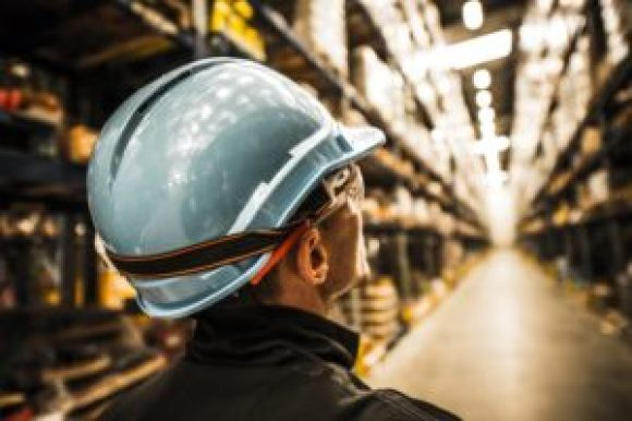 Man wearing a hard hat inside of a warehouse in the summer